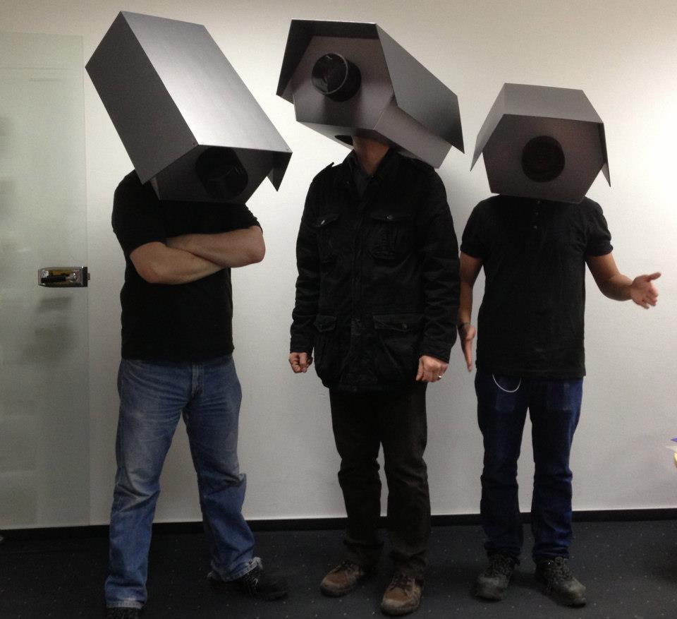 Drei Menschen, deren Köpfe in Papp-Kameras verschwinden