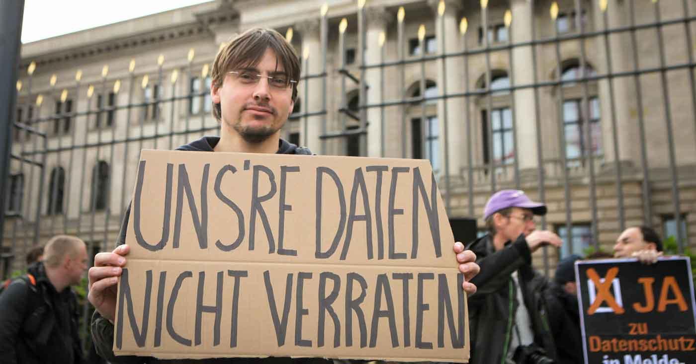 """Ein Mann hält ein Schild hoch auf dem steht """"unsere Daten nicht verraten"""""""