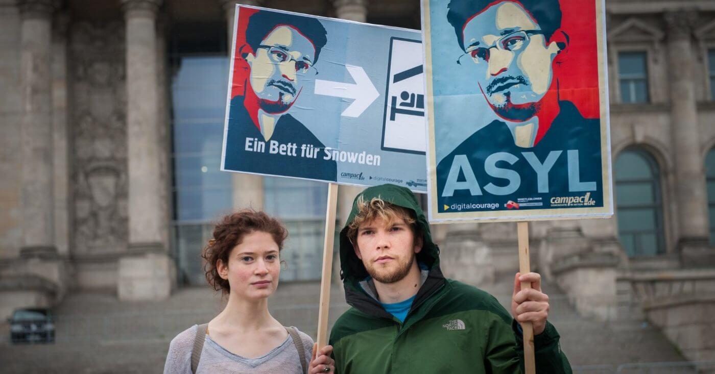 Zwei Demonstranten halten Schilder hoch: Ein Bett für Snowden, Asyl für Snowden