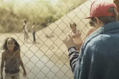 Ein Junge mit roter Kappe ist eingesperrt - der Zaun trennt ihn von der Außenwelt.