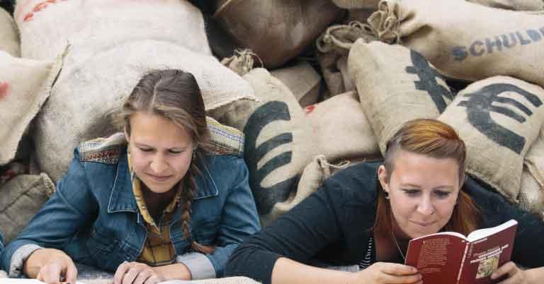 Zwei Studentinnen liegen unter großen Säcken voll Geld - symbolisch für die Schuldenberge ihrer Studiengebühren in NRW