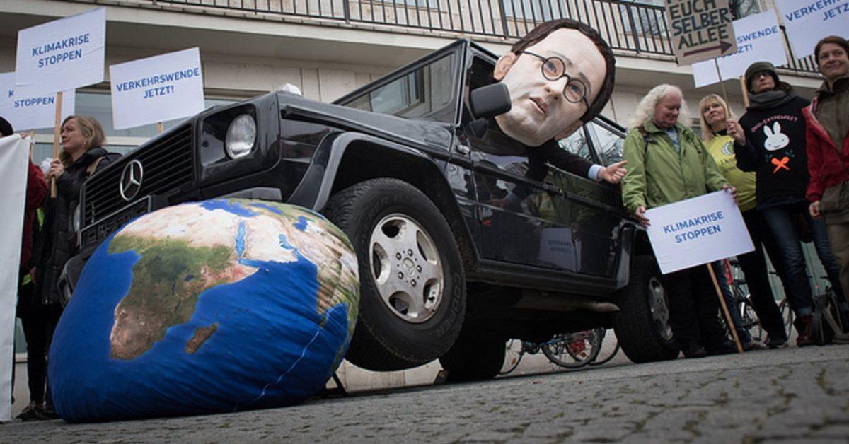 Campact-Aktion: Minister Andreas Scheuer überfährt im Geländewagen die Weltkugel