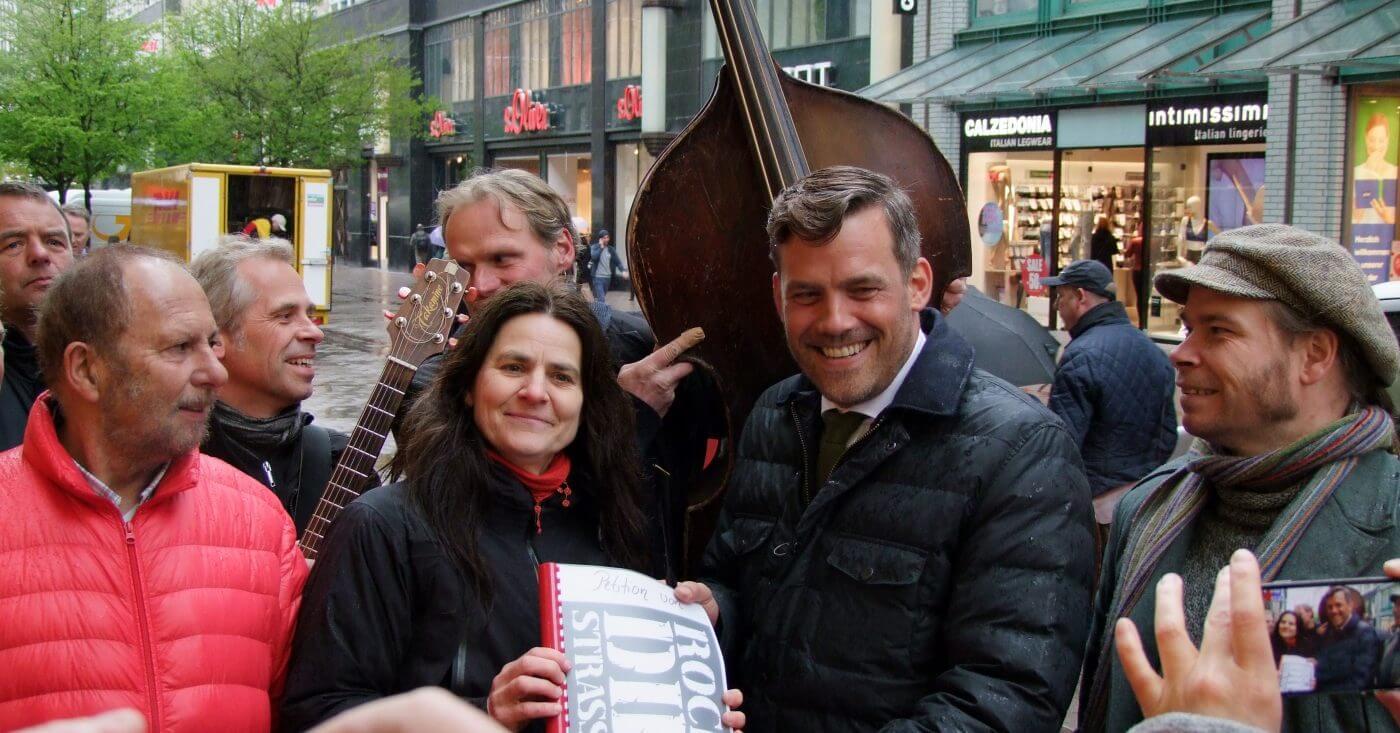 Straßenmusiker mit Instrumenten beim Überreichen ihrer Petition