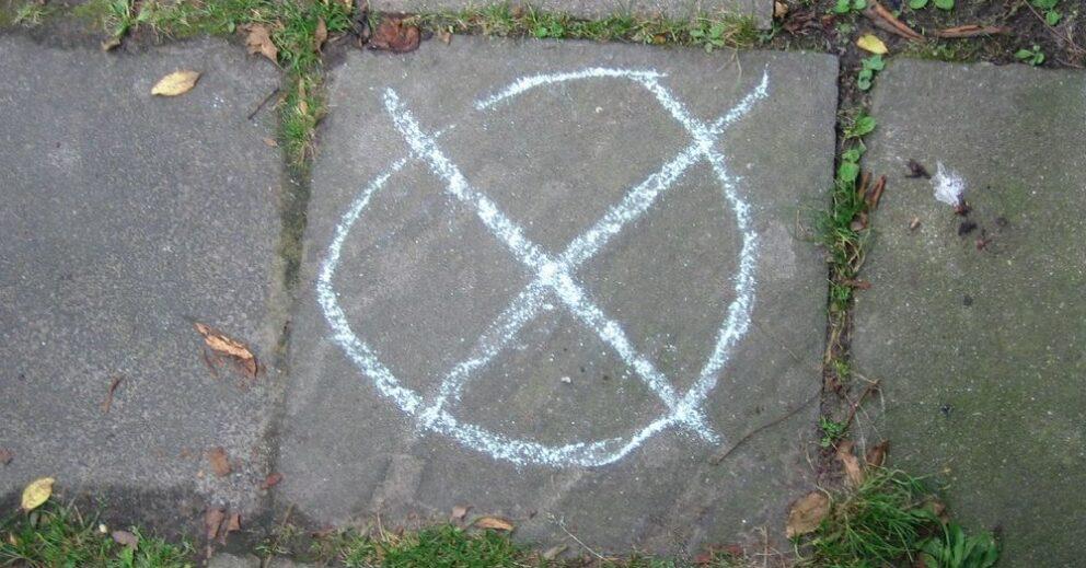 Ein Wahlkreuz ist mit Kreide auf den Boden gemalt