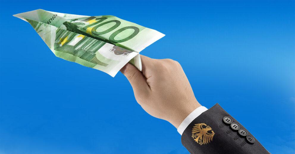 Hand in Anzugjacke mit Bundesadler hält einen Papierflieger aus einem Hundert-Euro-Schein