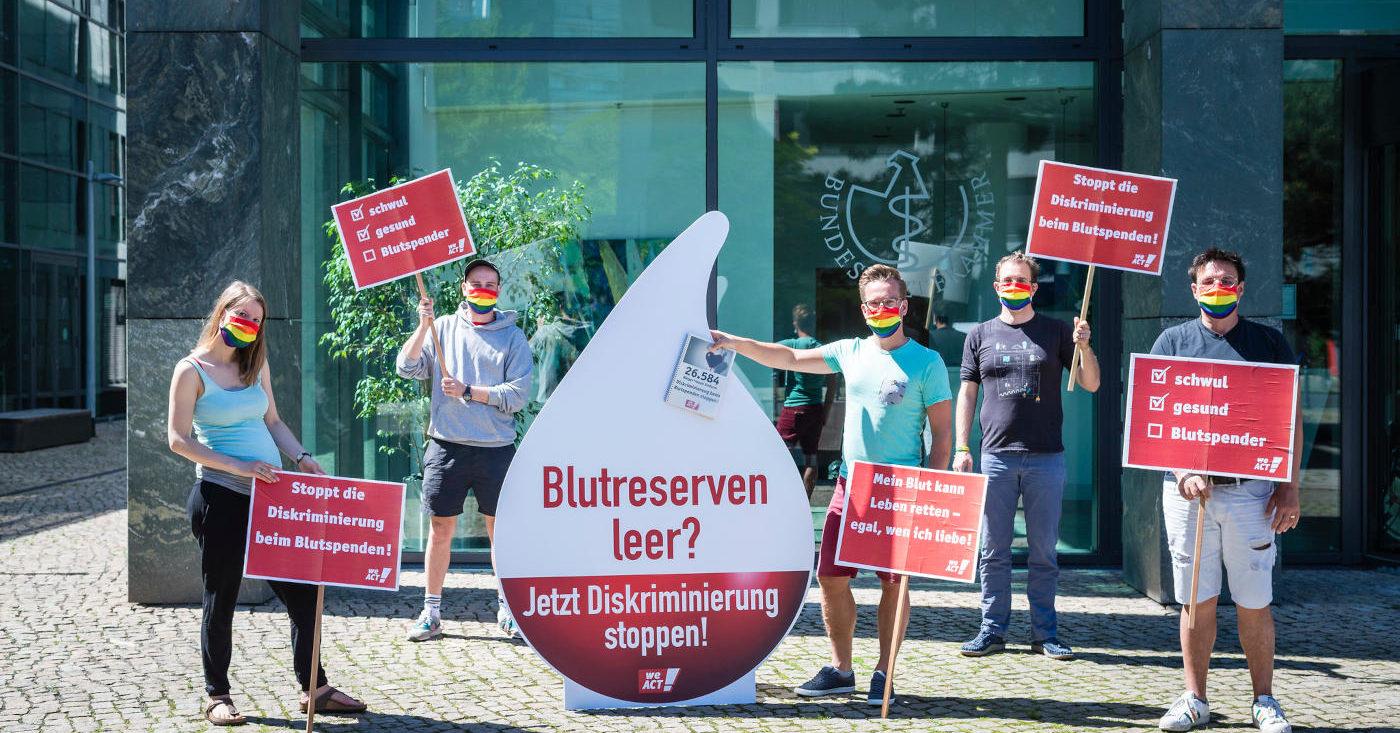 """Fünf Personen mit Regenbogenmundschutz und roten Transparenten zur WeAct-Petition """"Jetzt Diskriminierung beim Blutspenden stoppen"""" stehen vor der Bundesärztekammer in Berlin."""