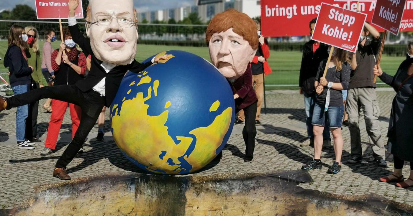 Menschen mit Altmaier- und Merkel-Maske tanzen um die Weltkugel. Stopp Kohle!