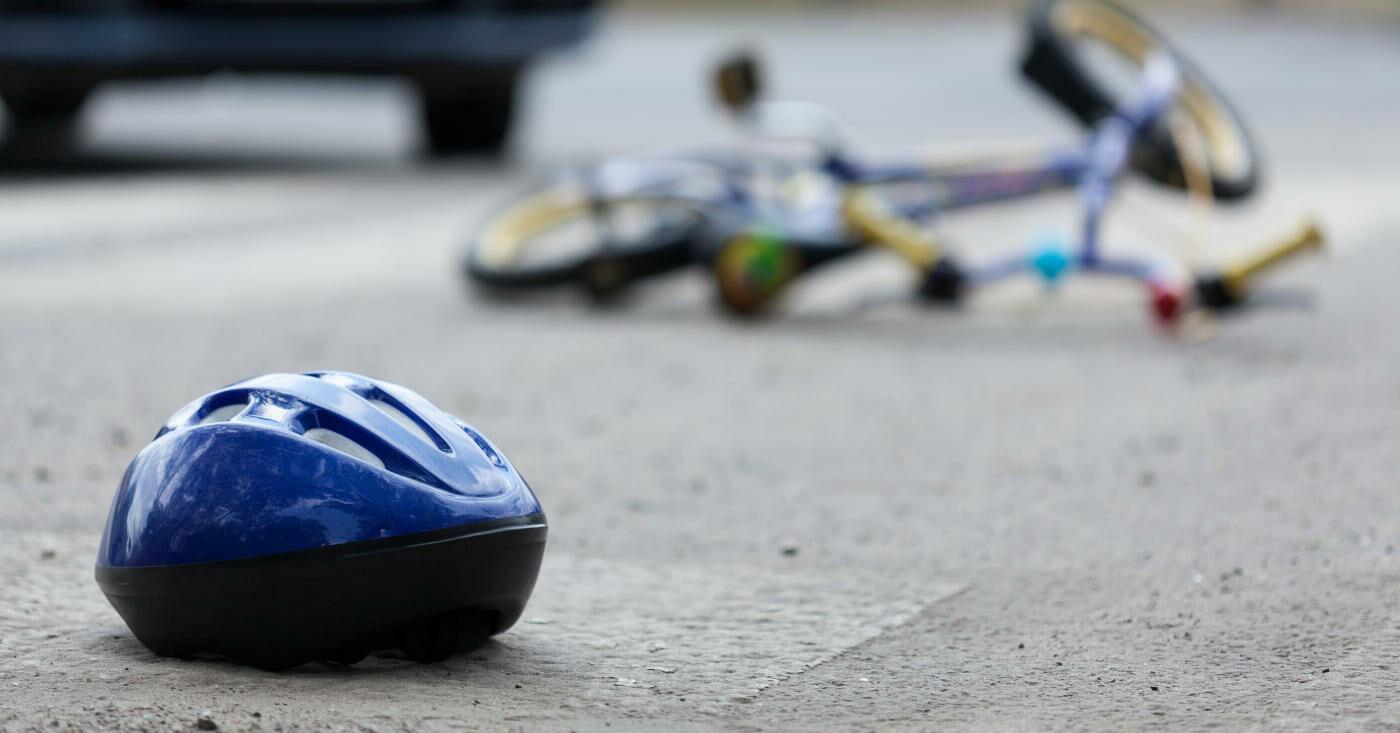 Ein Helm liegt auf der Straße, dahinter ein Fahrrad (Unfall-Symbolbild)