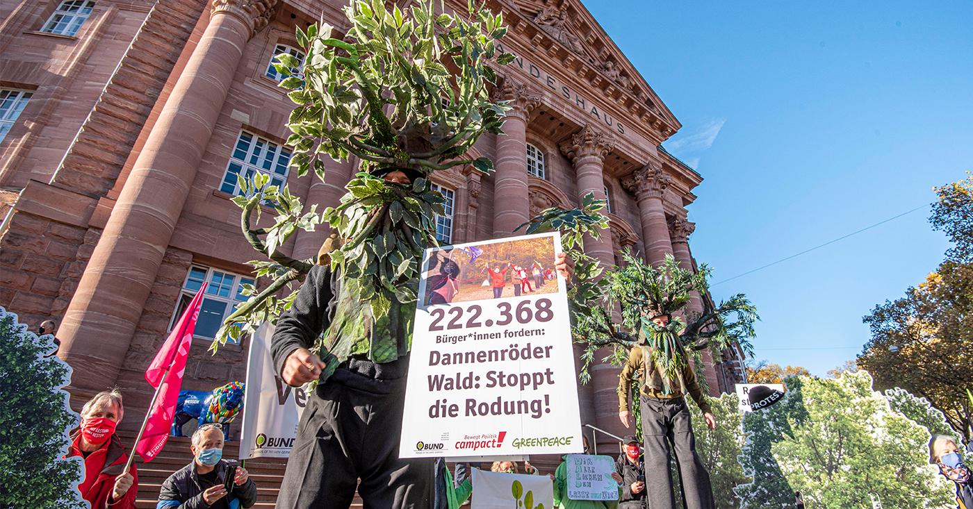 Unterstützer*innen von Campact, BUND und Greenpeace demonstrieren vor dem Landeshaus in Wiesbaden für den Erhalt des Dannenröder Waldes.