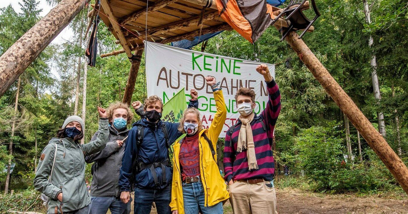 Wald statt Autobahnen: Proteste im Dannenröder Wald - fünf Personen strecken die linke Faust in die Luft