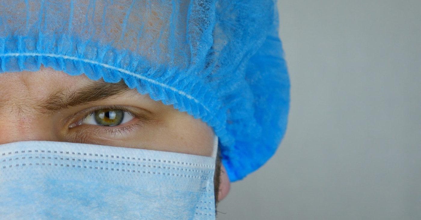 Ein Pfleger mit Maske und Haube schaut streng in die Kamera. Corona-Zuschuss jetzt.