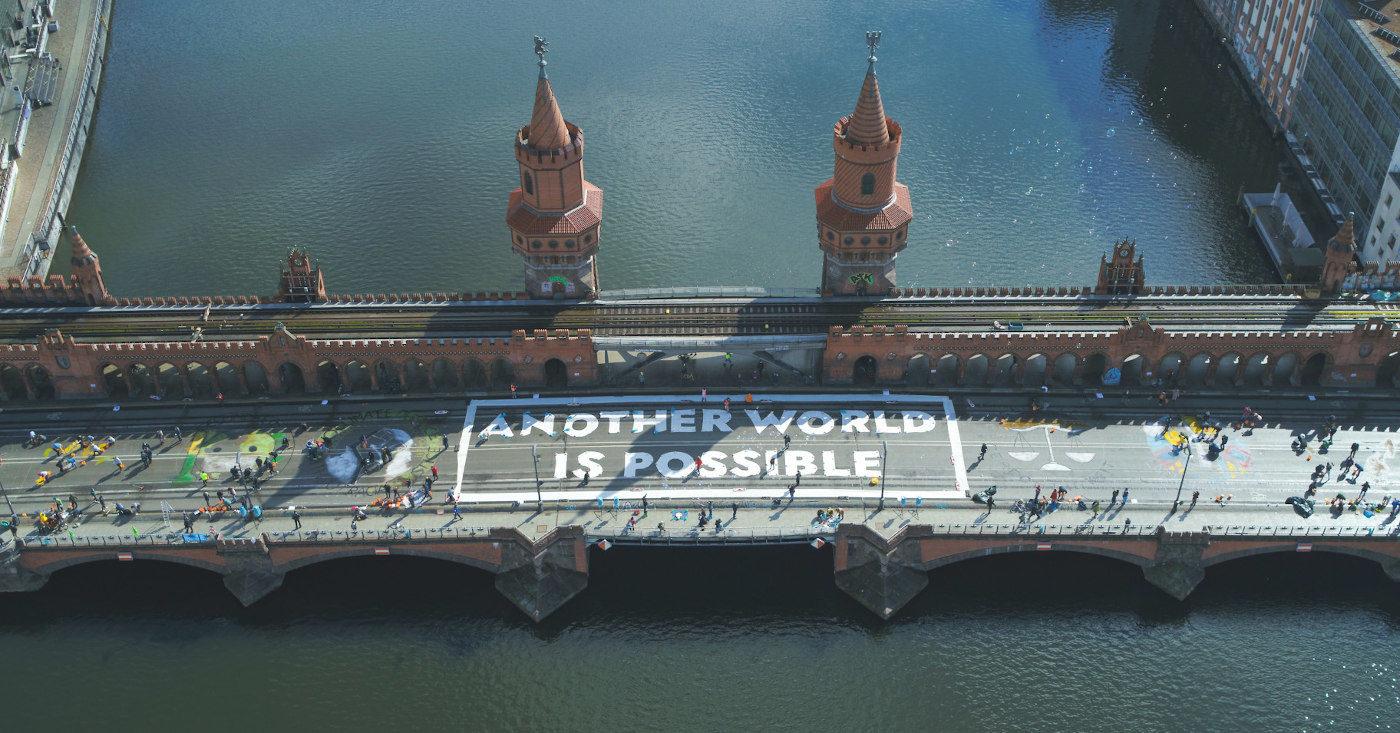 Panorama der Oberbaumbrücke über der Spree mit Fridays For Future Aktivisten, die mit weißer Farbe die Buchstaben Another World is Possible auf die Brücke gemalt haben . Rechts und links von der Aufschrift werden weitere Bilder mit bunter Farbe gemalt.