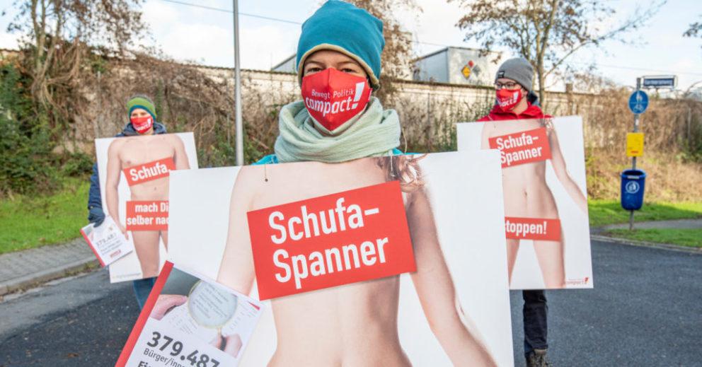 Eine Person mit Campact-Maske demonstriert vor der Schufa in Wiesbaden. Sie trägt ein Plakat, auf dem eine nackte Person zu sehen ist und die Aufschrift: Schufa-Spanner stoppen!