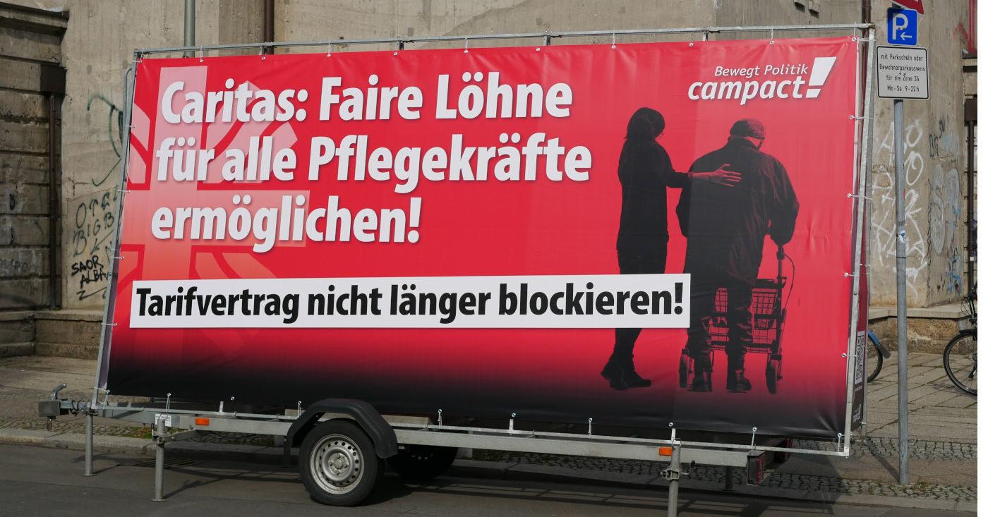 """Foto von einem mobilen Aufsteller mit dem Transparent zum Campact-Appell: """"Caritas: Faire Löhne für alle Pflegekräfte ermöglichen"""" Eine Person stützt eine andere Person am Rollator."""