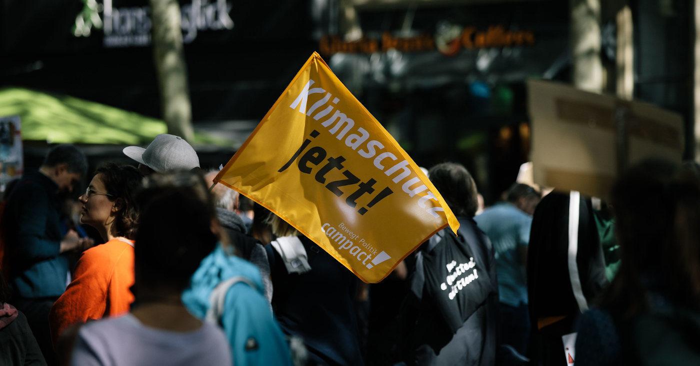 """Ein Bild von einer Klima-Demo: Darauf ist eine Campact-Fahne zu sehen auf der """"Klimaschutz jetzt!"""" steht."""