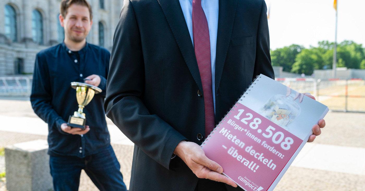 """Eine Person der SPD hält ein Ringbuch mit dem Campact-Appell """"128.508 Bürger*innen fordern: Mieten deckeln-überall"""". Dahinter steht eine weitere Person und hält einen Pokal."""