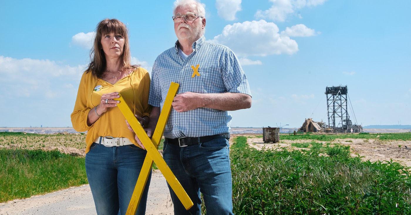 Marita Dresen und Helmut Kehrmann wohnen am Tagebau Garzweiler II in Nordrhein-Westfalen. Sie halten ein gelbes X aus Holz vor dem Körper. Mit ihrer WeAct-Petition fordern sie: Kein weiteres Dorf mehr für Kohle.
