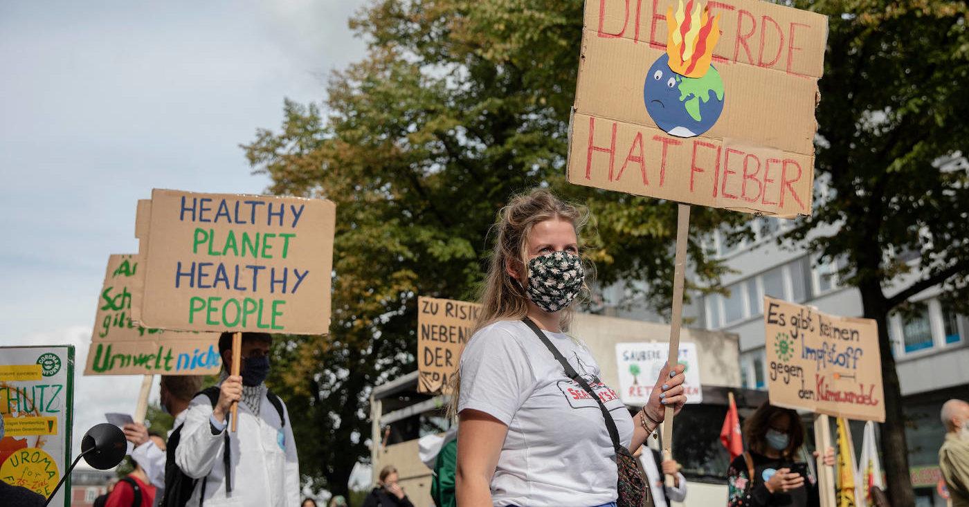 Einige Personen demonstrieren für den Klimaschutz mit Pappschildern.