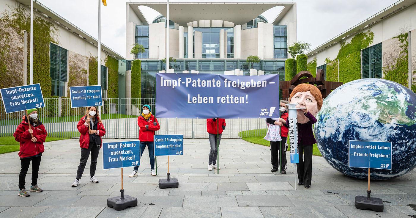 Campact-Aktive demonstrieren für Freigabe der Impfpatente mit einer aufblasbaren Weltkugel und einer Merkel-Schauspielerin, die eine große Spritze hält