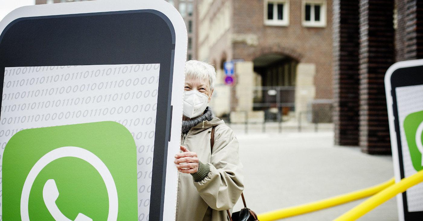 Eine Person steht halb hinter einem großen Smartphone aus Pappe. Sie demonstriert gegen die neuen WhatsApp-Nutzungsbedingungen vor der Facebook-Zentrale in Hamburg.