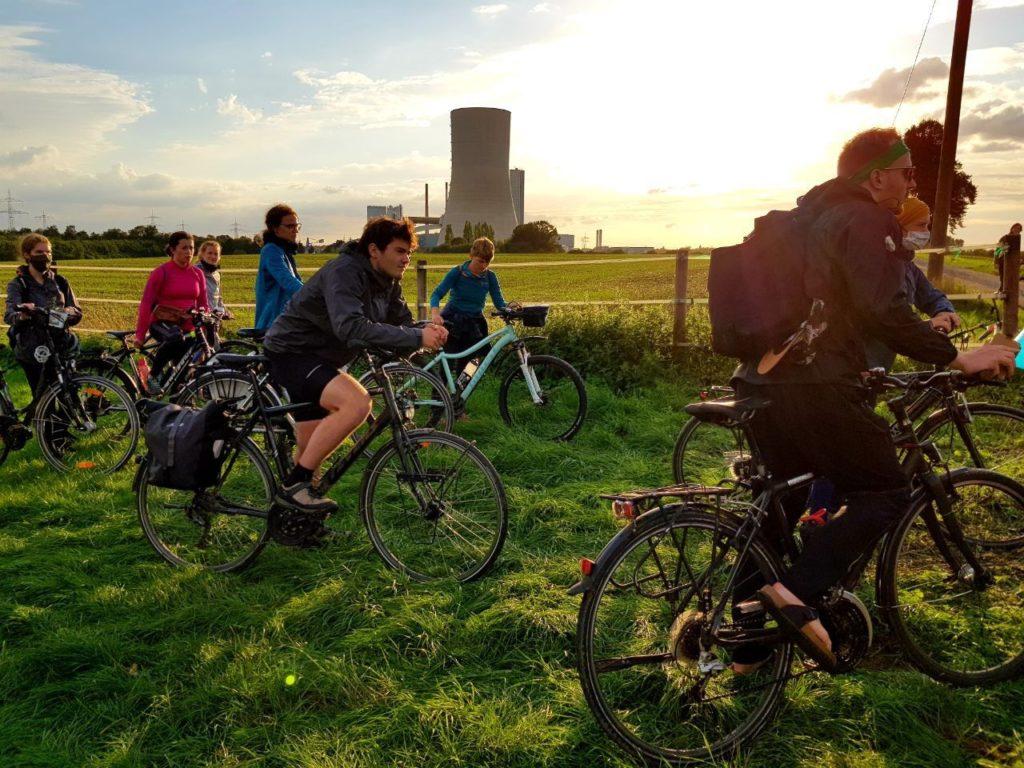 Radfahrer und Radfahrerinnen der Initiative Students for Future stehen auf einer Wiese.