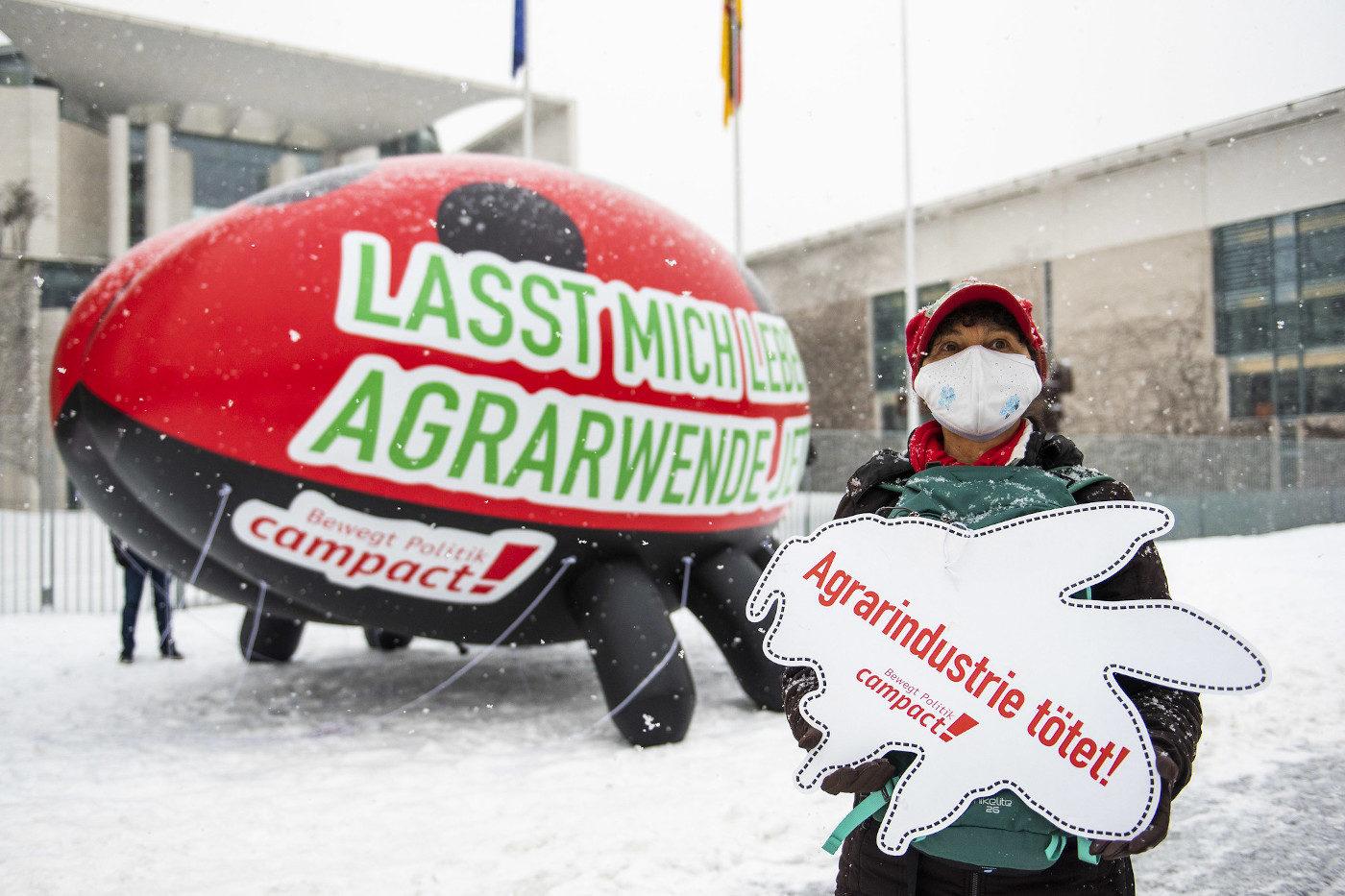 """Ein großer, aufblasbarer Marienkäfer steht vor dem Kanzleramt in Berlin, davor eine Campact-Aktive mit einem Schild, auf dem steht: """"Agrarindustrie tötet!"""""""