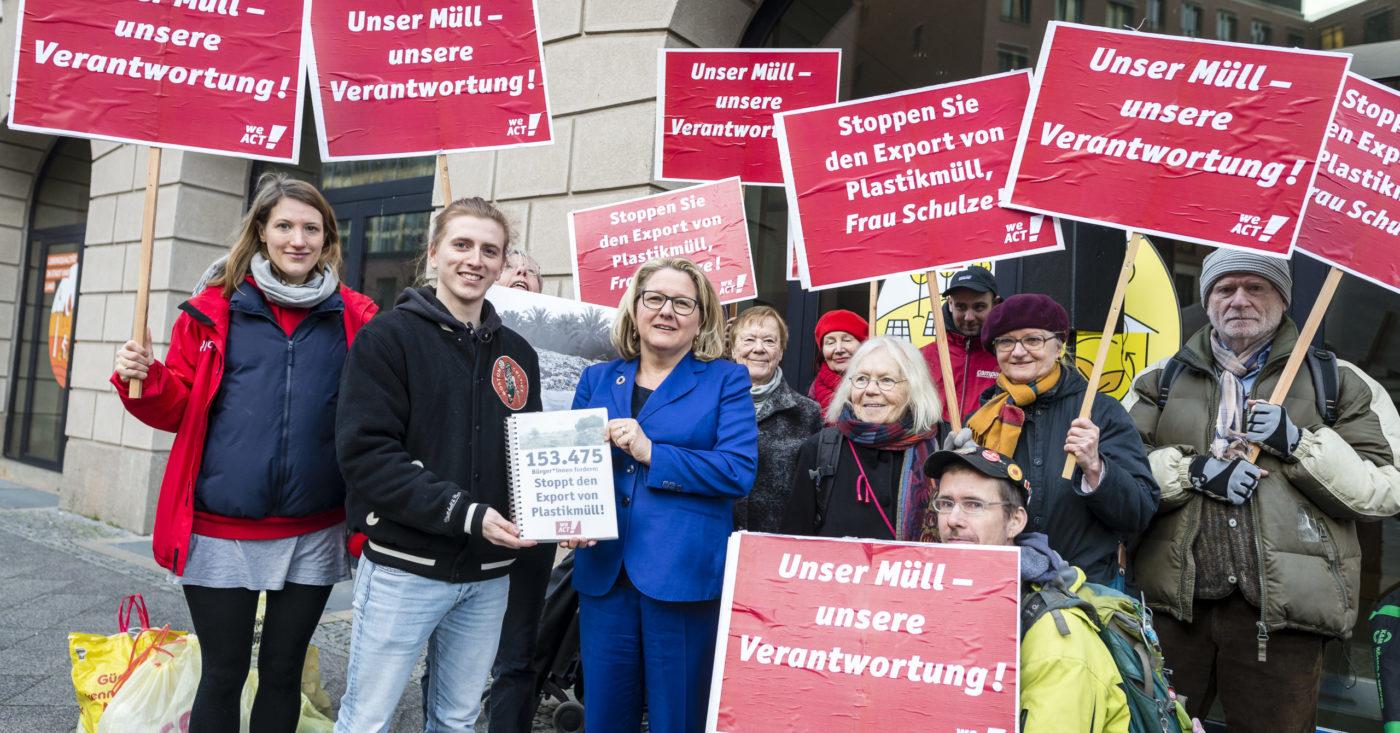 Der Student Max übergibt seine Petition an Umweltministerin Svenja Schulze. Im Hintergrund halten Demonstant*innen Schilder gegen den Export von Plastikmüll. Auch Du kannst wie Max etwas bewegen! Starte Deine eigene Petition auf WeAct.