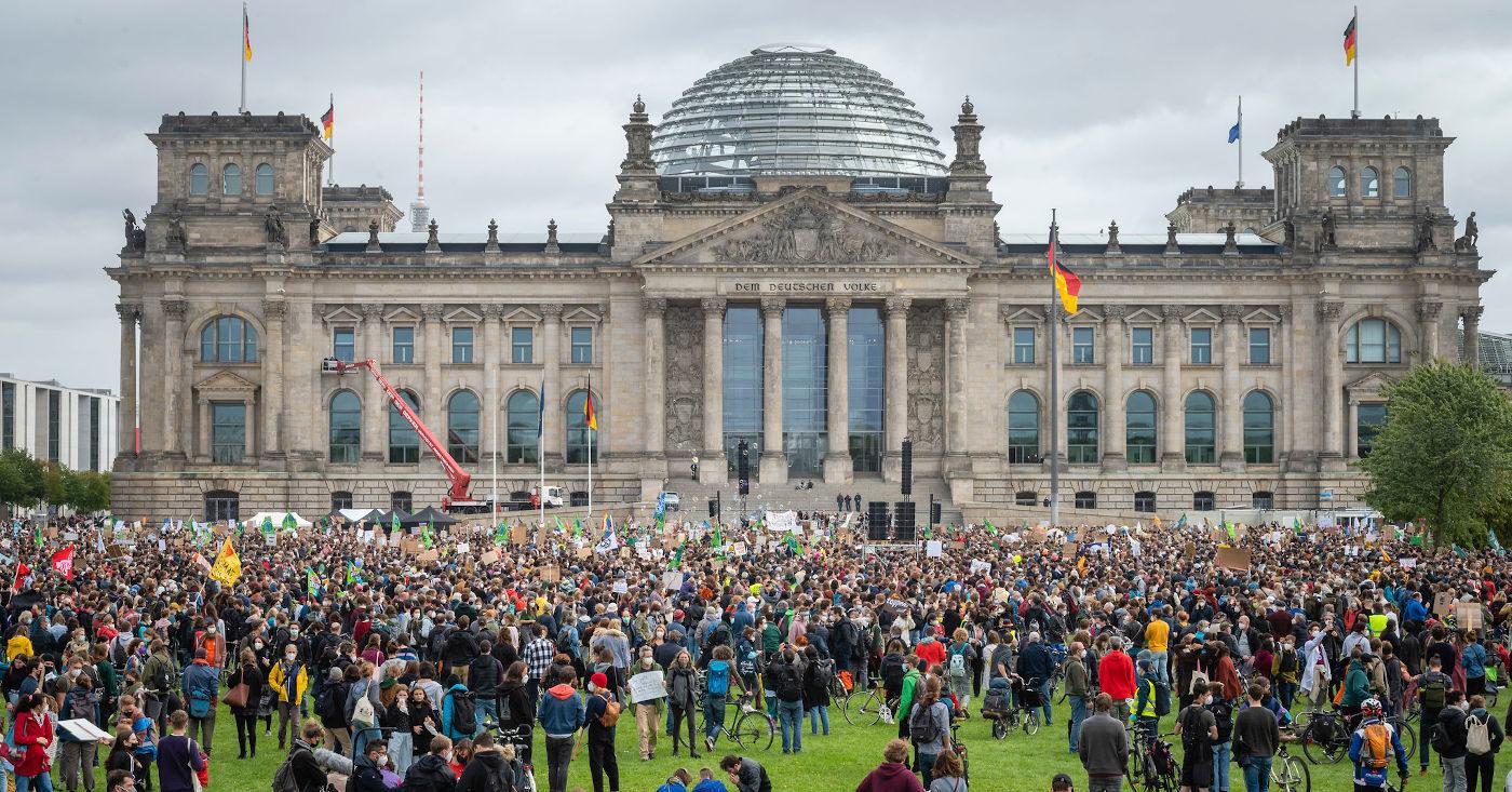 Tausende Klima-Demonstrant*innen mit Pappschildern und Fahnen stehen vor dem Reichstag in Berlin.