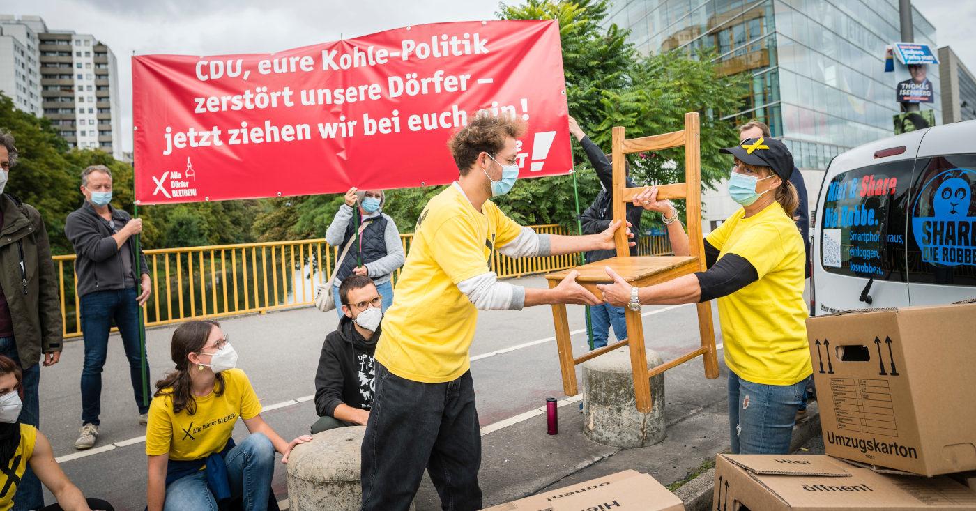 """Vor dem Konrad-Adenauer-Haus räumt eine Gruppe von Alle Dörfer bleiben einen Umzugstransporter aus. Im Hintergrund halten Personen ein rotes Banner mit der Schrift """"CDU, eure Kohle-Politik zerstört unsere Dörfer - jetzt ziehen wir bei euch ein!"""""""